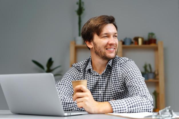 그의 작업 테이블에 노트북에서 일하는 젊은 남자를 닫습니다.