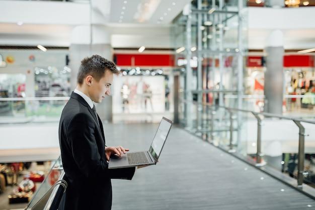 モール、屋内、縦断ビュー、ビジネスセンターで黒のスーツを着て、ラップトップに取り組んでいる若い男
