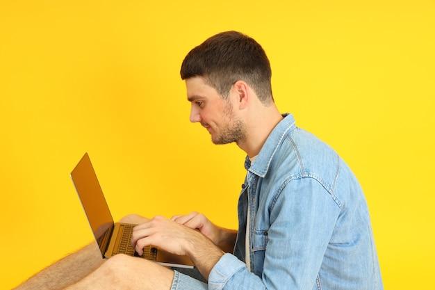Молодой человек, работающий на ноутбуке на желтом фоне.