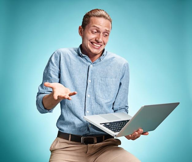 Молодой человек работает на ноутбуке