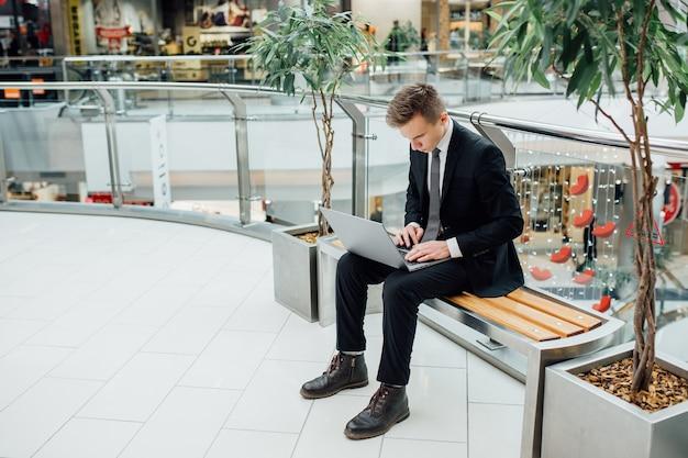 Молодой человек, работающий над ноутбуком в черном костюме, торговый центр, серьезные молодые бизнесмены, сел