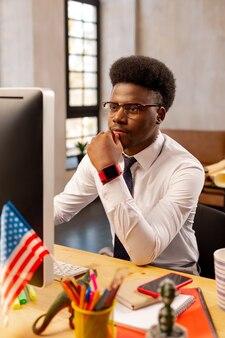 オフィスに座ってコンピューターで作業している若い男