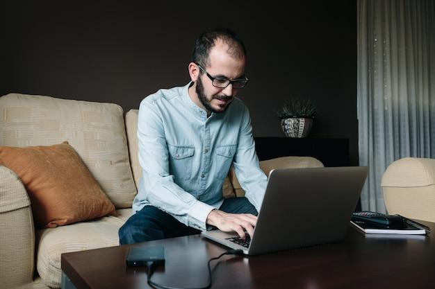 Молодой человек работает онлайн с ноутбуком, сидя на диване во второй половине дня у себя дома