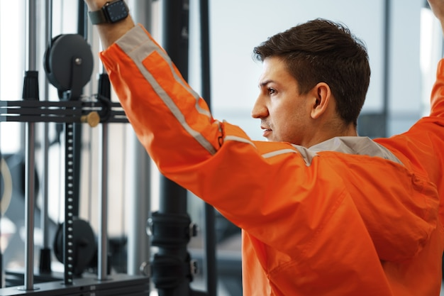 Young man working out training back muscles in the gym
