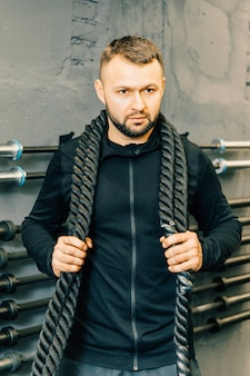Young man working out with battle ropes at a gym