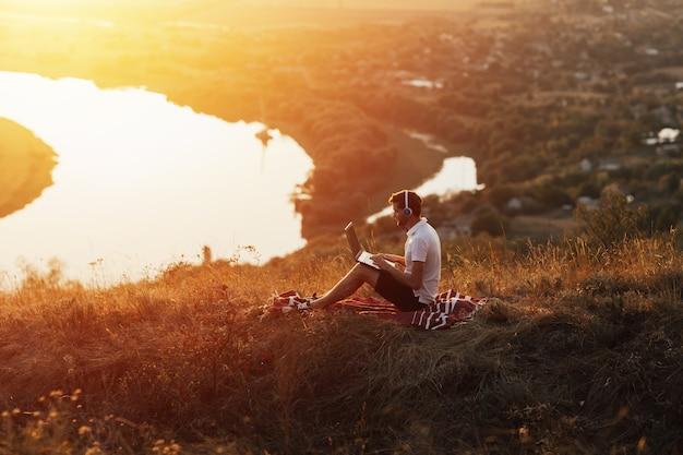 야외에서 노트북으로 일하는 젊은 남자. 그는 강 일몰에 언덕 꼭대기에 앉아