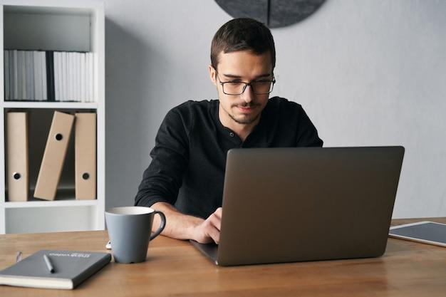 커피를 마시는 동안 테이블에서 컴퓨터 전화와 태블릿으로 작업하는 젊은 남자