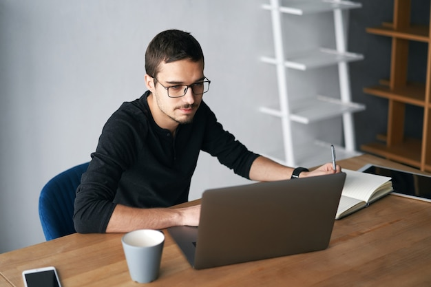 Young man working with computer phone and tablet at the table while drinking coffee