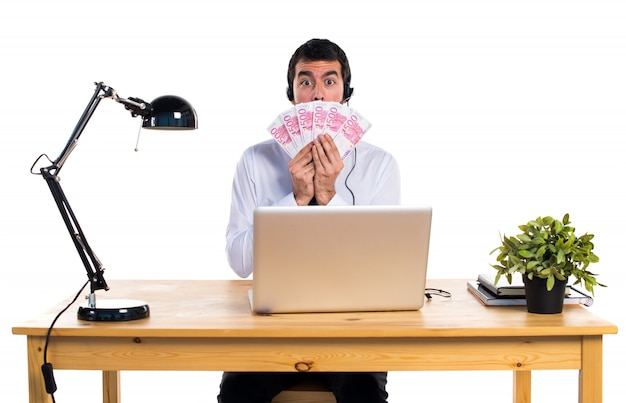 Young man working with a headset taking a lot of money