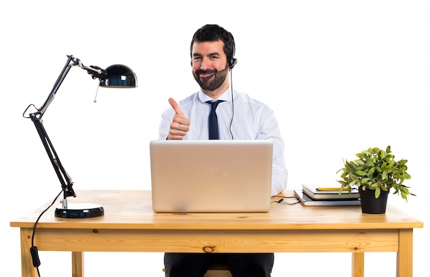 Young man working with a headset with thumb up
