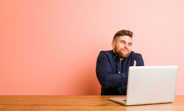 ラップトップで作業している若い男は、のんびりと幸せに笑って、自分を抱きしめます。