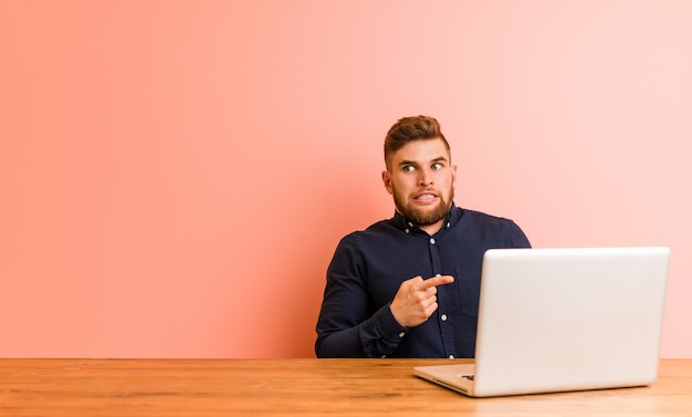 Young man working with his laptop shocked pointing with index fingers to a copy space.