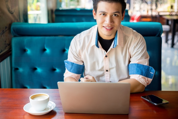 Young man working with laptop in cafe