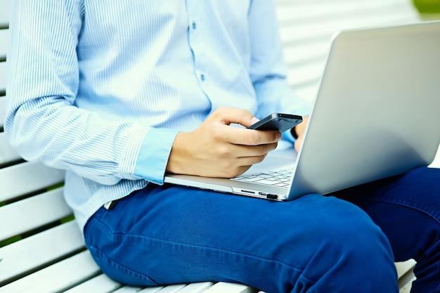 Молодой человек, работающий с ноутбуком, мужские руки на ноутбуке, деловой человек в повседневной одежде на улице