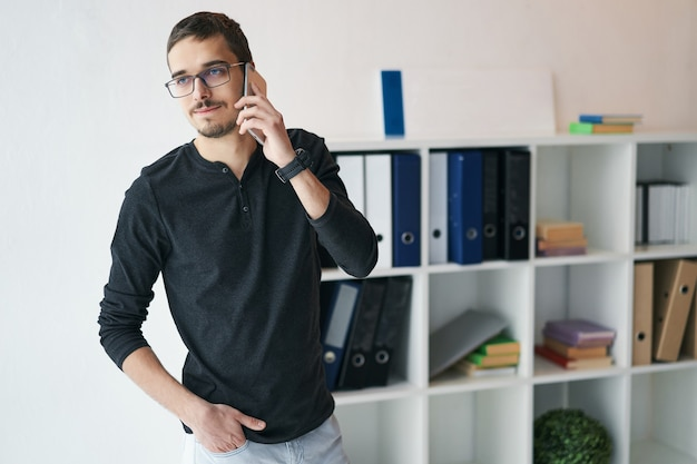 Young man working with phone and computer receiving phone call talking with partners