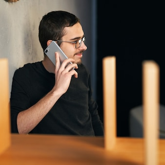 Young man working with phone and computer, receiving phone call, talking with partners