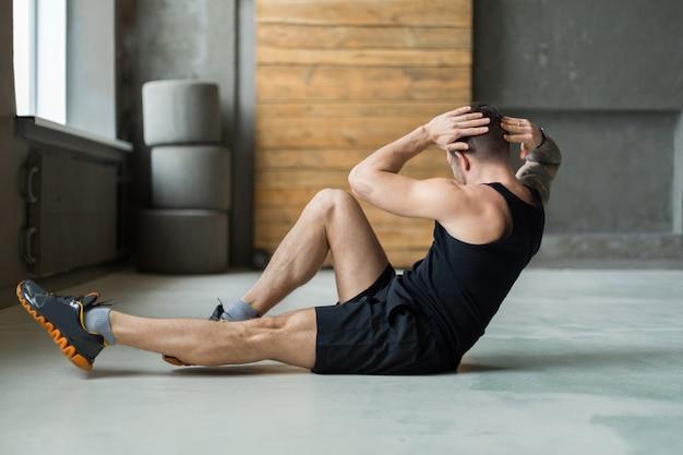 피트니스 클럽에서 젊은 남자 운동. 백인 남자의 초상화 운동, 윗몸 일으키기 및 복근 근육을위한 십자가 위기, 실내 훈련