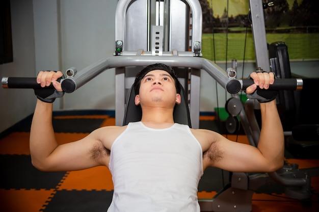 Тренировки молодого человека в спортзале фитнеса