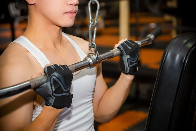 Young man workouts at fitness gym