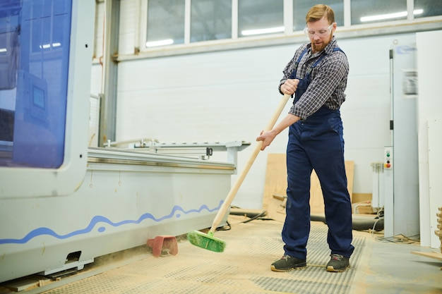Young man in workwear sweeping floor