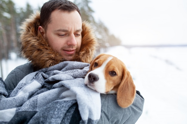 A young man wrapped his best friend beagle dog in a warm blanket to warm him