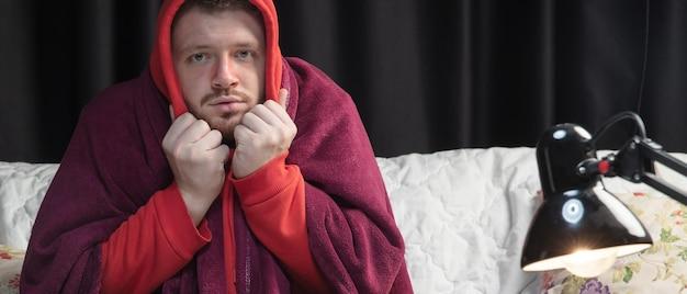 격자 무늬에 싸인 젊은 남자는 집에서 집에 있는 소파에 앉아 아프고, 아프고, 재채기하고, 기침하는 것처럼 보입니다. 건강 관리 및 의학, 질병 예방, 계절 질병 증상 및 자기 보호. 전단