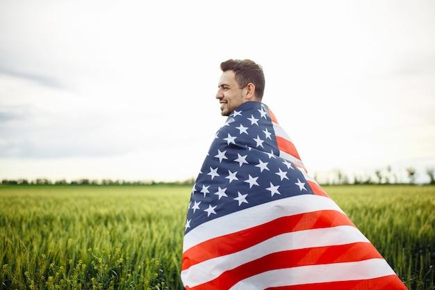 Молодой человек, завернутый в американский флаг на зеленом поле пшеницы