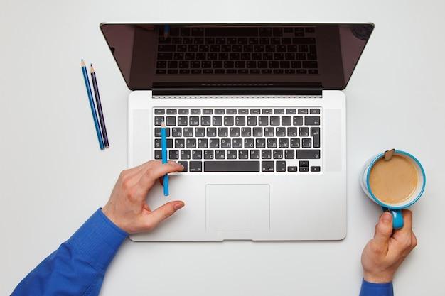 若い男がコーヒーを飲みながらノートパソコンにテキストメッセージを書き込みます