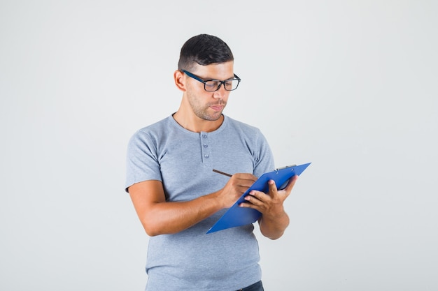 Young man writing on clipboard with pencil in grey t-shirt, glasses