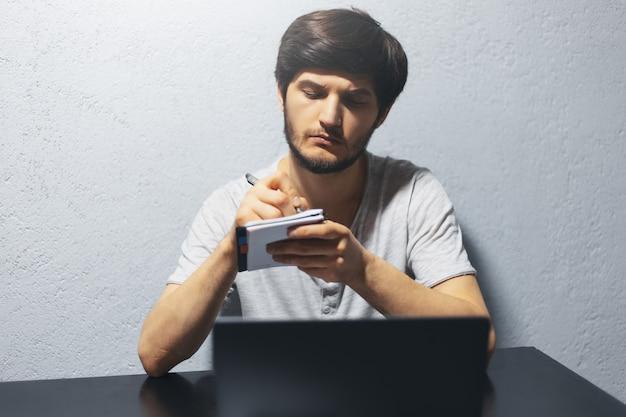 ノート用紙に書いている若い男。ラップトップで、黒いテーブルで作業しています。
