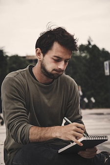 Young man writing in notebook at nature, side view. profile of bearded man drawing
