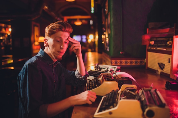 Young man writing on old typewriter. in dark lighting, restaurant, modern clothes, old writer habits