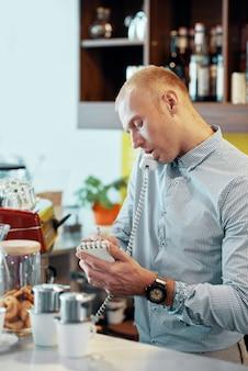 若い男がカフェテリアでクライアントの注文を書く
