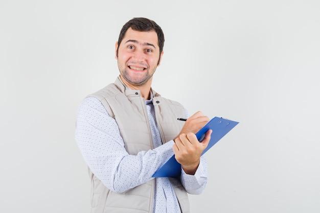 Giovane che scrive qualcosa sul taccuino con la penna e posa in giacca beige e sembra ottimista, vista frontale.