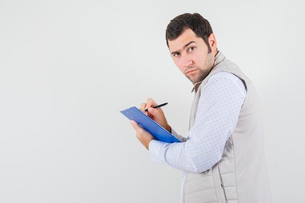 Giovane che scrive qualcosa sul taccuino con la penna e posa in giacca beige e sembra serio, vista frontale.