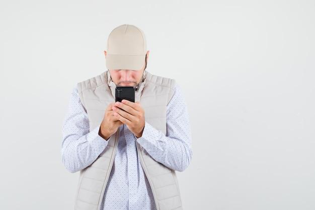ベージュのジャケットとキャップで携帯電話にテキストを書いて、集中して見える若い男。正面図。
