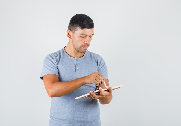 Young man writing with chalk at blackboard in grey t-shirt front view.
