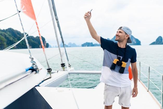 若い男のヨットは、電話でselfieを作ります。旅行とアクティブな生活。贅沢な休暇