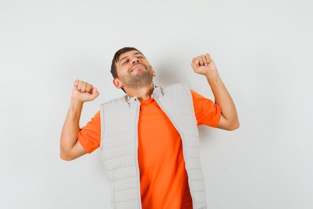 Молодой человек зевает и потягивается в футболке, куртке и выглядит расслабленным.