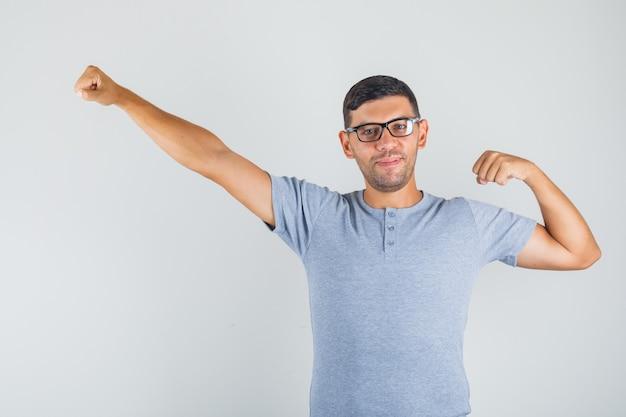 若い男のあくびをし、灰色のtシャツ、メガネで笑顔とリラックスした探して