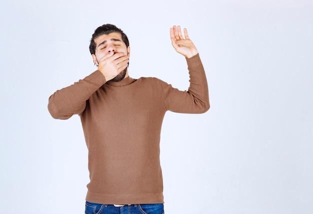 彼の口の上に手であくびをしている若い男。