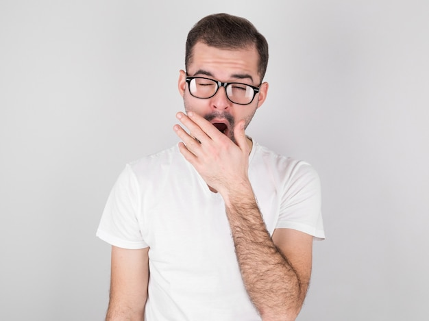 若い男は灰色の壁に対する倦怠感からあくびをします Premium写真
