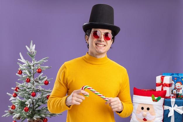 Giovane uomo in dolcevita giallo e occhiali indossando il cappello nero tenendo il bastoncino di zucchero in piedi accanto a un albero di natale e regali su sfondo viola