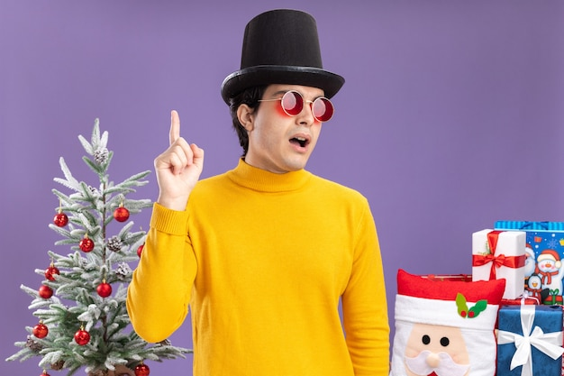 Young man in yellow turtleneck and glasses wearing black hat looking aside surprised showing index finger having great idea standing next to a christmas tree and presents over purple wall