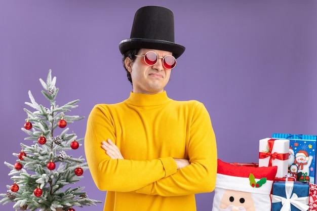 Giovane uomo in dolcevita giallo e occhiali indossando il cappello nero guardando la telecamera scontento con le braccia incrociate sul petto in piedi accanto a un albero di natale e presenta su sfondo viola