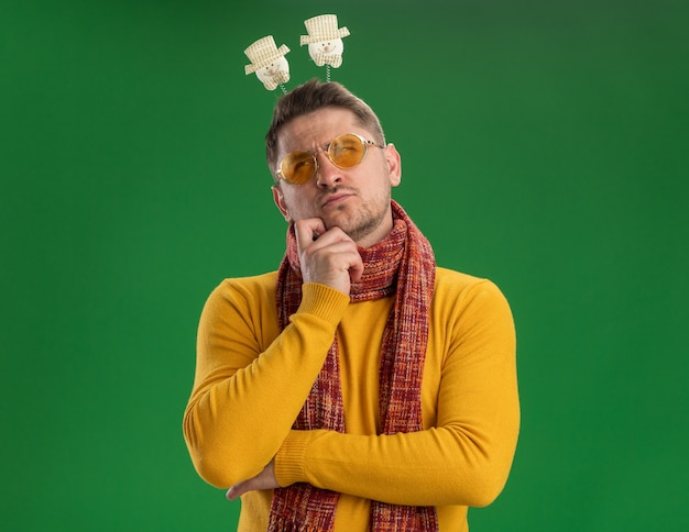Young man in yellow turtleneck and glasses with warm scarf and funny rim on head looking up with pensive expression on face thinking standing over green wall