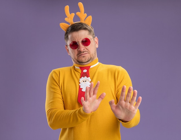 Young man in yellow turtleneck and red glasses wearing funny red tie and rim with deer horns