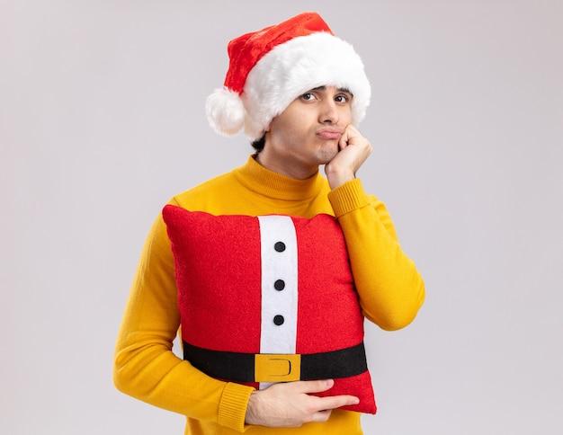 Giovane uomo in dolcevita giallo e cappello santa tenendo il cuscino di natale guardando la fotocamera stanco e annoiato in piedi su sfondo bianco