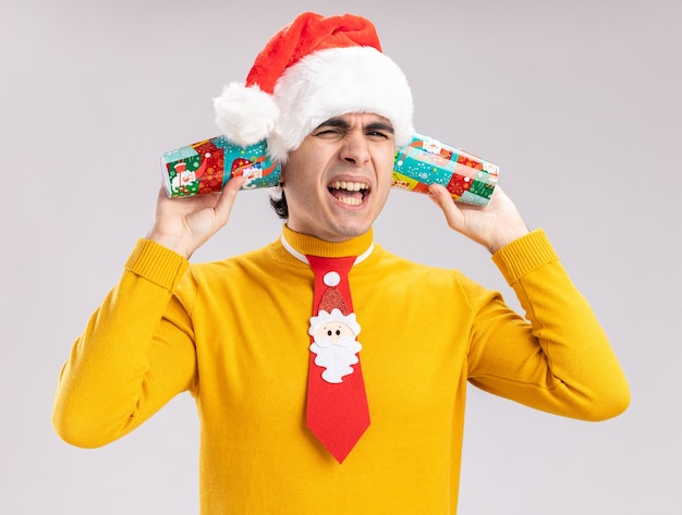 Young man in yellow turtleneck and santa hat with funny tie holding colorful paper cups over his ears yelling with annoyed expression standing over white wall