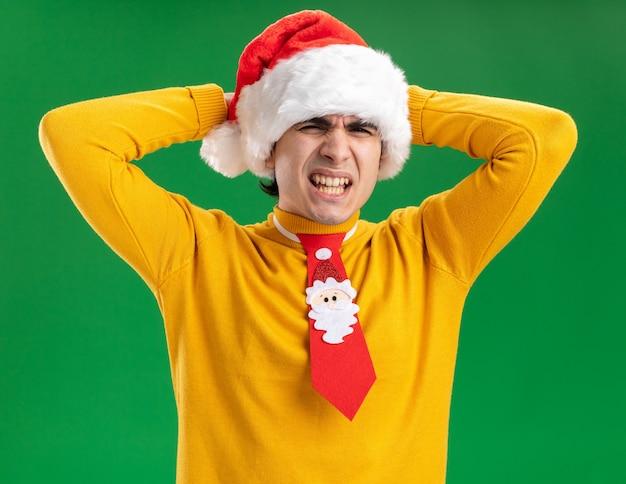 Giovane uomo in dolcevita giallo e cappello da babbo natale con cravatta divertente che sembra infastidito e irritato con le mani sulla testa in piedi su sfondo verde